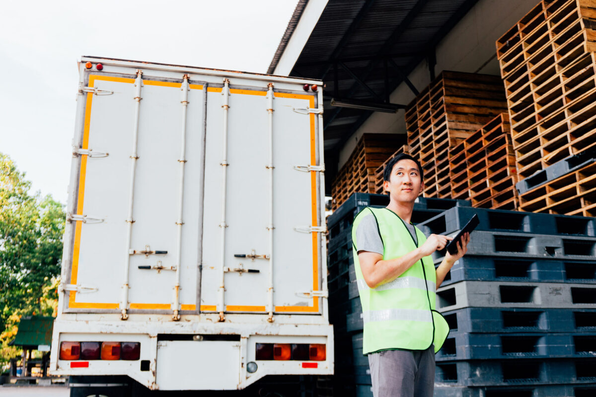 Young man at warehouse distribution facility uses a tablet to plan logistics.